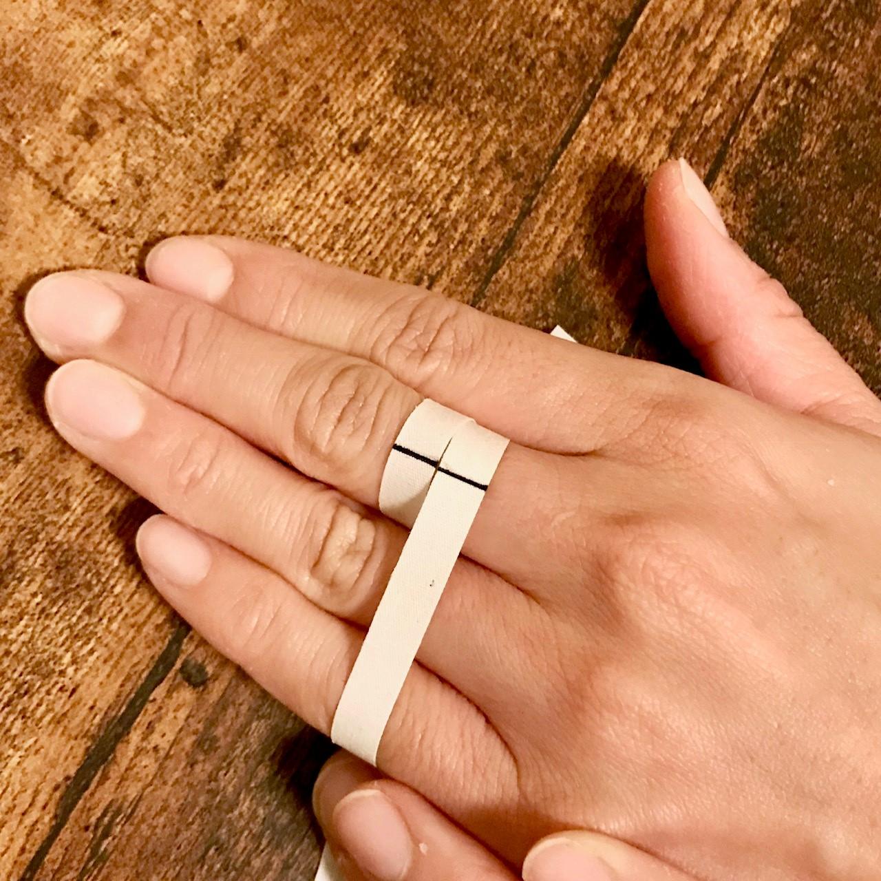 <p>測定したい指の一番太い部分(第2関節より少し下辺り)にヒモ、又は紙を巻き付けます。※この時のフィット感が指輪をはめた時の感覚に近いです。円周1mmの違いで1サイズぐらいの差が出ますので、ゆるくならないように注意して巻き付け具合を調節しましょう。一周巻き付けて重なった部分にペンで目印を付けます。<br>※見やすいように少し太めのヒモを使用し、太めの印を付けています。